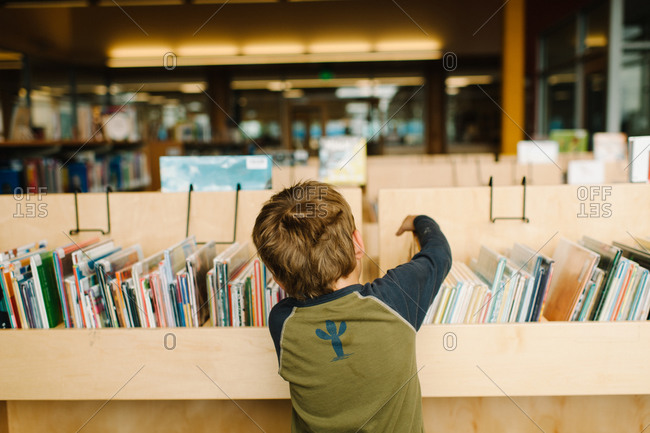 A boy looking from a book in the library