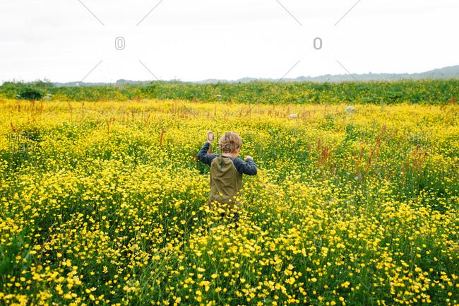 A boy running in a field of buttercups