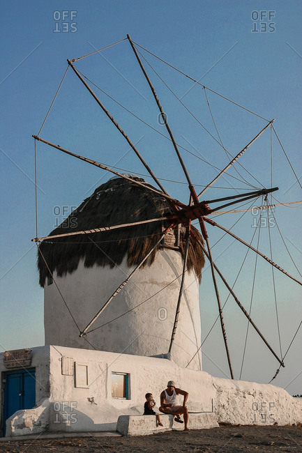 Mykonos Greece - July 6, 2005: Man and child resting by a traditional windmill in Mykonos, Greece