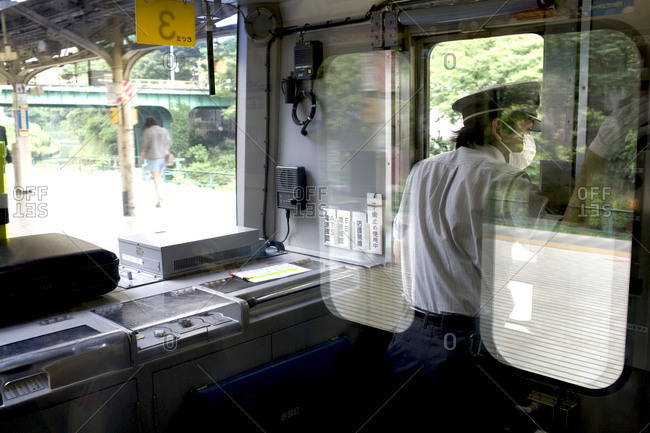 Tokyo, Japan - June 20, 2010: Train operator looking out of window on the JR Sobu Line