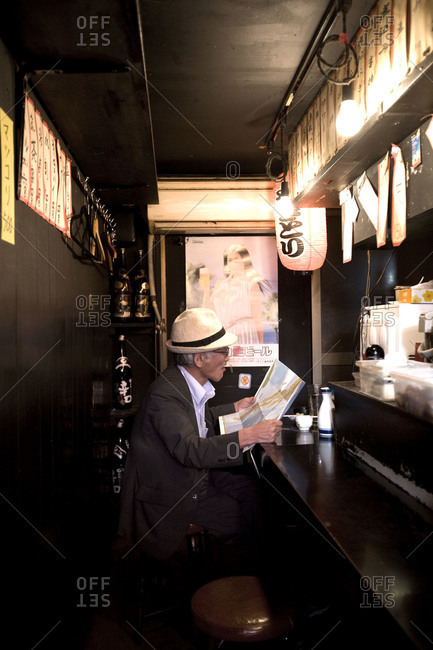 Tokyo, Japan - June 16, 2010: Side view of a man watching map at a typical Yakitori restaurant