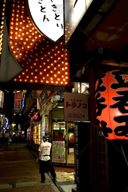 Tokyo, Japan - June 21, 2010: Japanese chef standing in front of a restaurant at night