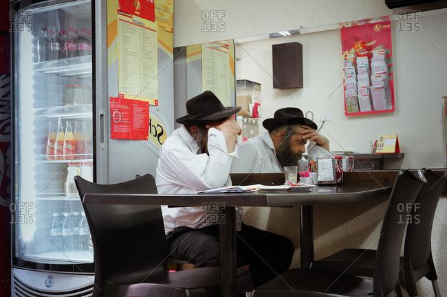 Jerusalem Israel - April 30, 2013: A Jewish gentleman sitting in a cafe reading