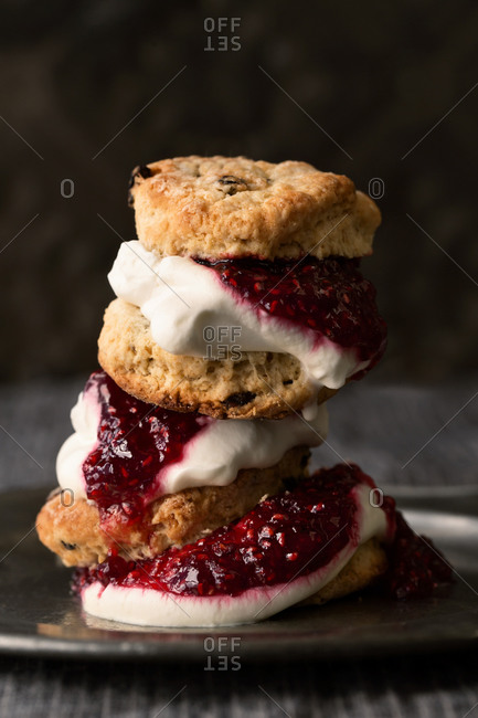Stack of scones with whipped cream and raspberry jam