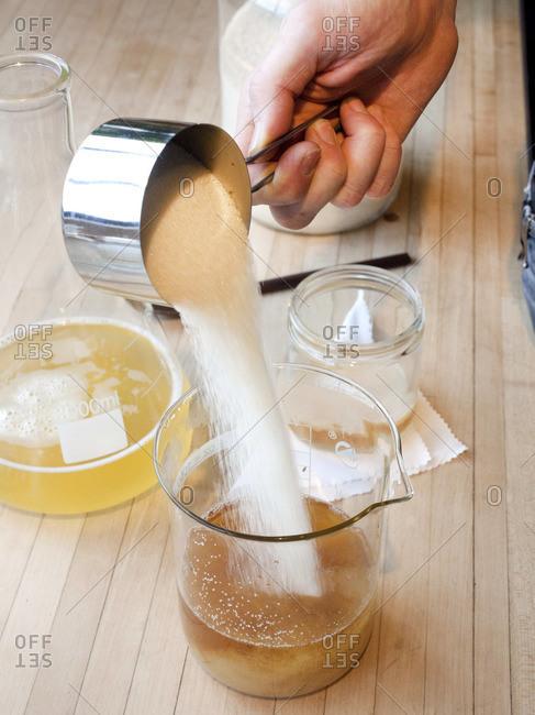Person pouring sugar into strained kombucha tea