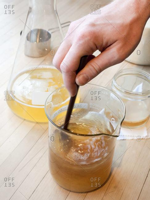 Person stirring sugar into strained kombucha tea