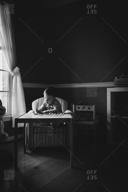 Boy writing a note on a table