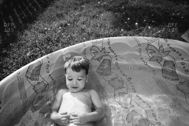 Little boy lying in a kiddie pool