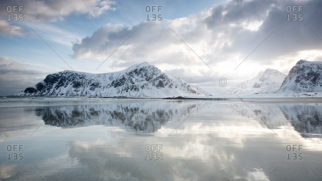 Reflections of snowy mountains in Flakstad, Norway