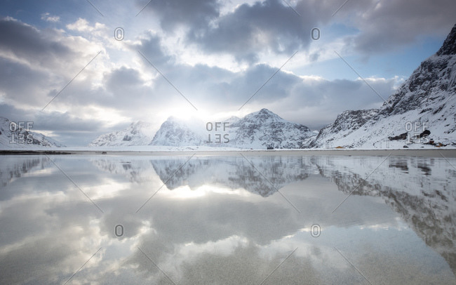 Reflections of snowy mountains and clouds in Flakstad, Norway