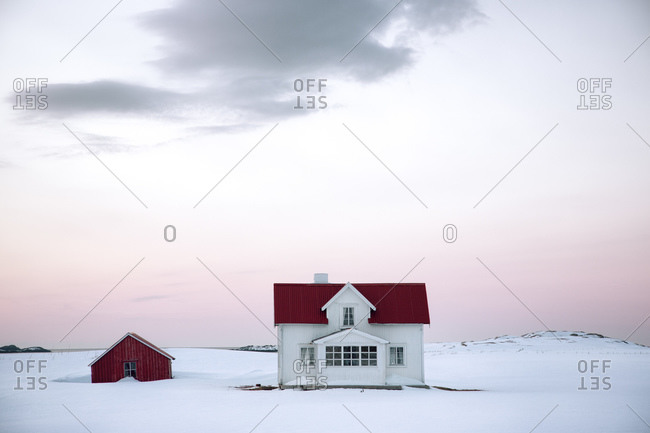 House in a snow-covered field in rural Norway