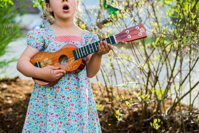 Young girl in dress playing ukulele and singing