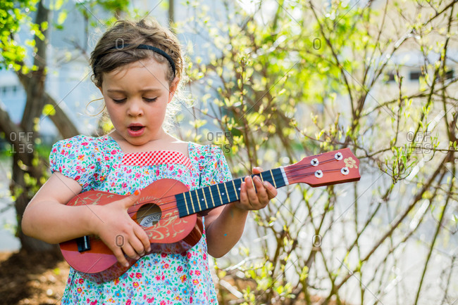 Young girl in dress looking down, playing ukulele and singing