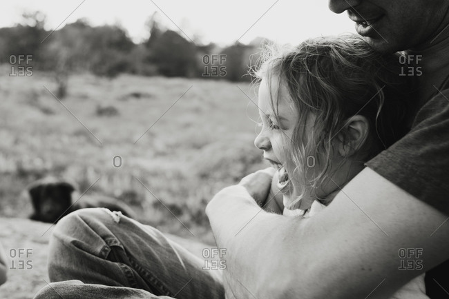 Black and white portrait of father hugging daughter