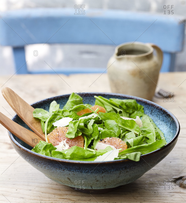 Close up of bowl of fresh green salad with grapefruit and shredded parmesan cheese