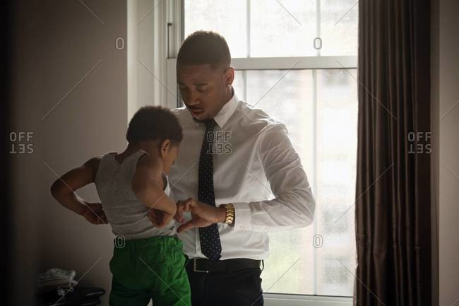 Man helping son get dressed by window