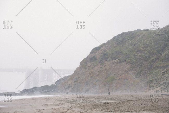 Foggy beach with bridge in background
