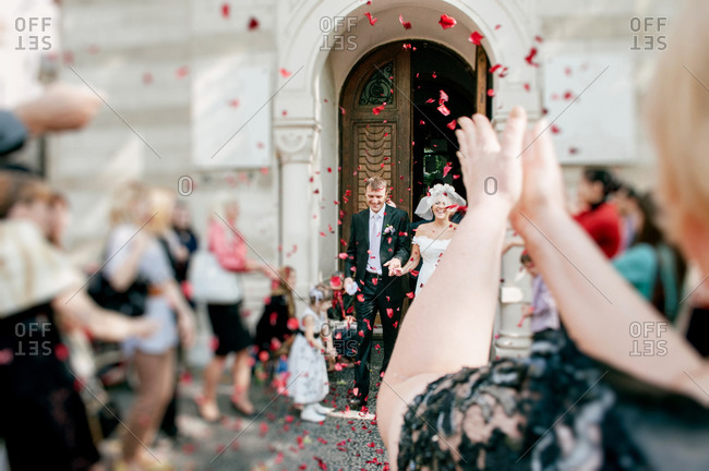 People throwing rose petals over newlywed couple