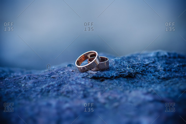 Close up of wedding rings on a rock