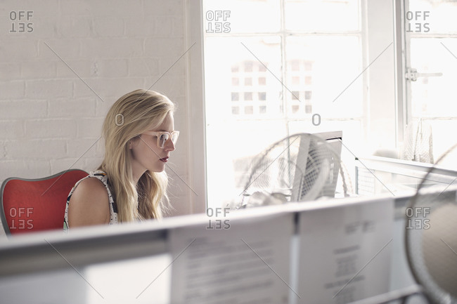 Blonde woman working in an office cubicle