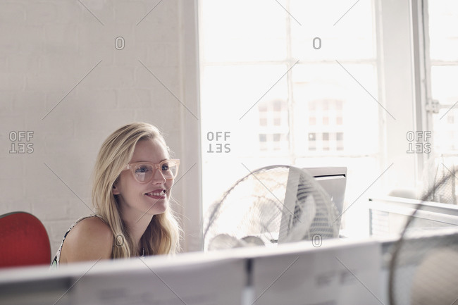 Blonde woman smiling in her cubicle