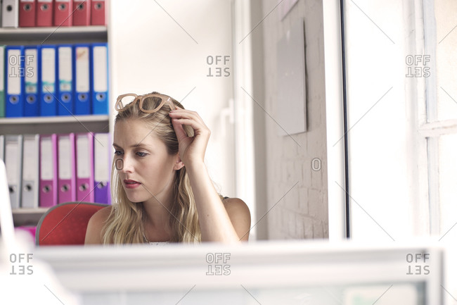 Blonde woman touching her glasses in an office