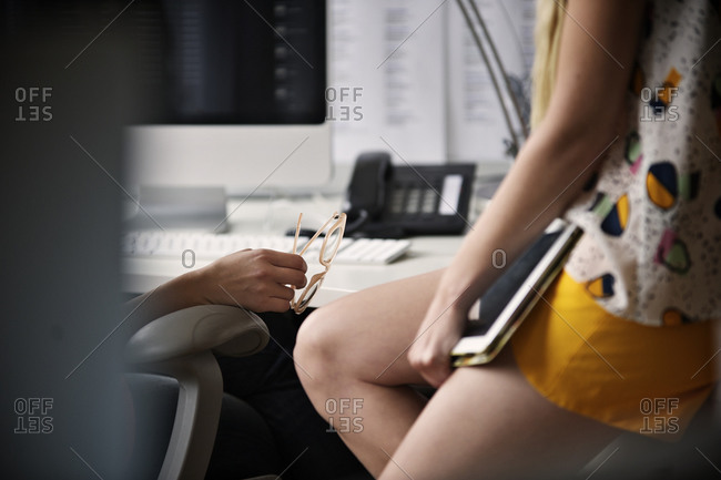 Woman leaning on an office table with a tablet in her hands