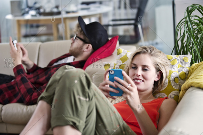 People looking at their smartphones on a couch