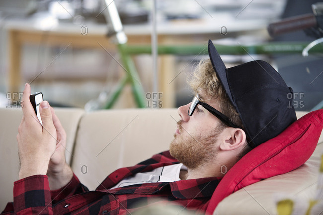 Young man looking at his smartphone on a couch