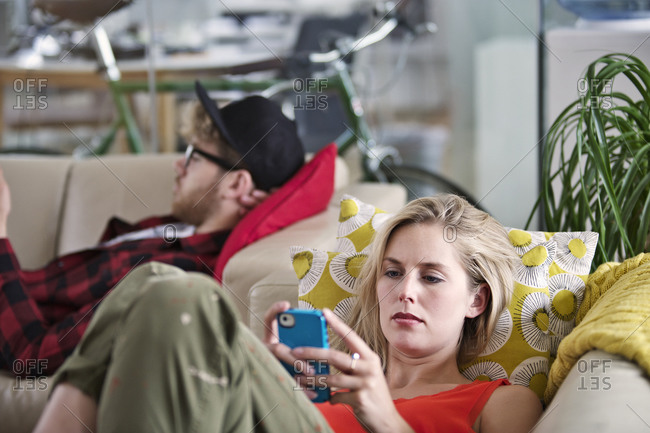 Woman looking at her smartphone on a couch