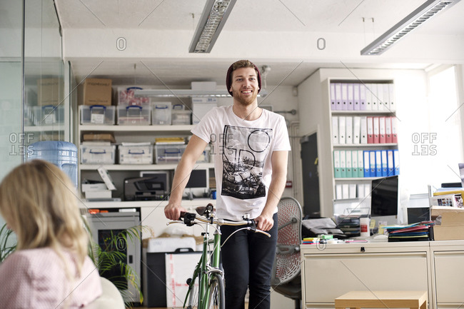 Young man with a bicycle in an office
