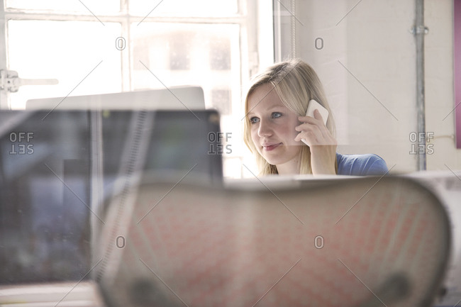 Young woman having a phone call in the office