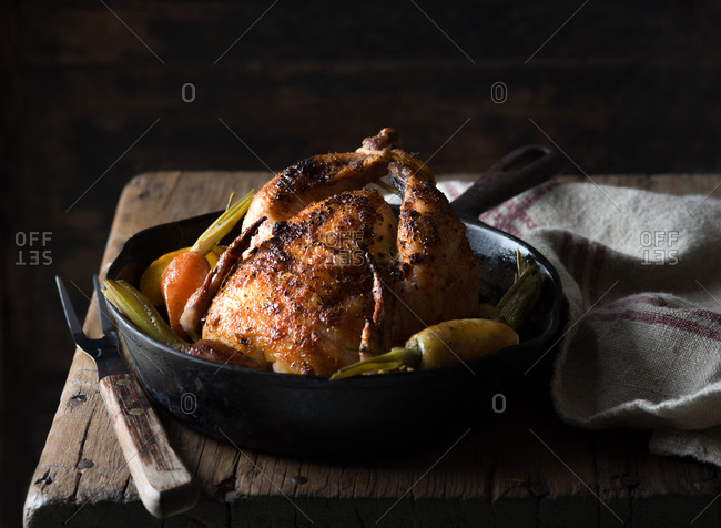 Roasted Cornish game hen with onions and carrots