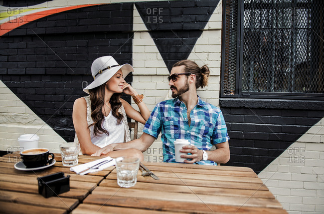 Young couple having coffee outside