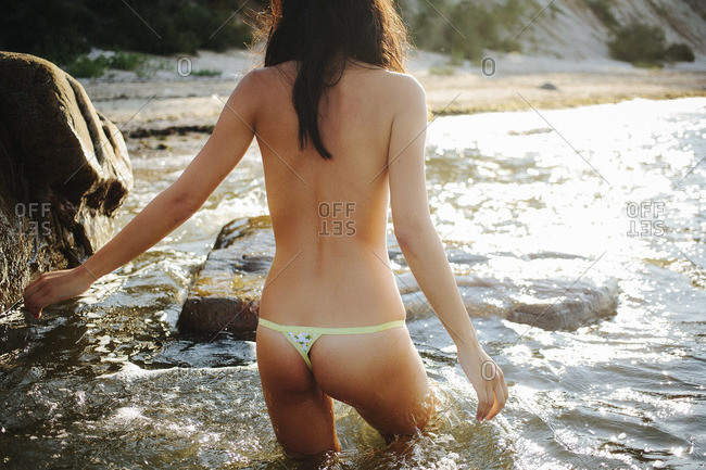 Read view of a young topless woman wading in the ocean