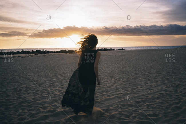 Woman in maxi dress running on a beach