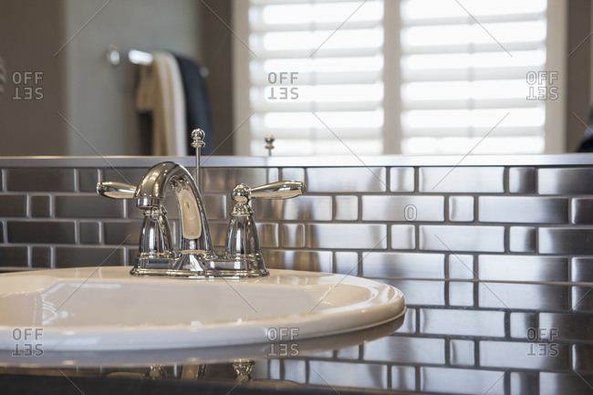 Faucet and spigots at sink with metallic backsplash in bathroom