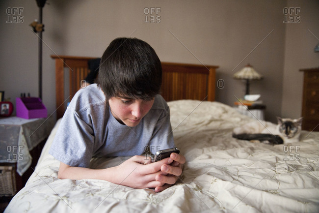A teenage boy is busy on his cell phone at his home in Lincoln, Nebraska.