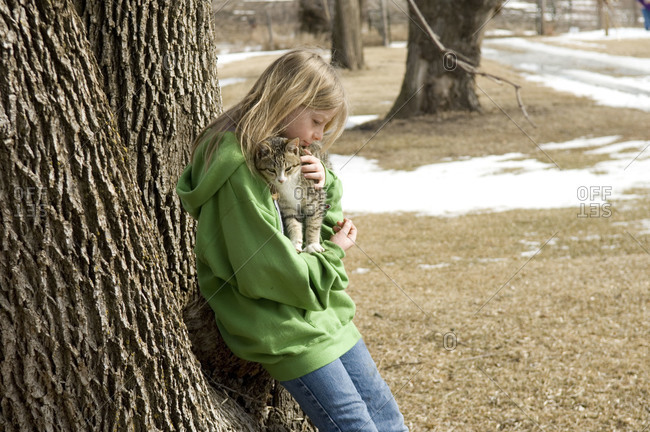A young girl plays with a cat at an abandoned farm in Nebraska.