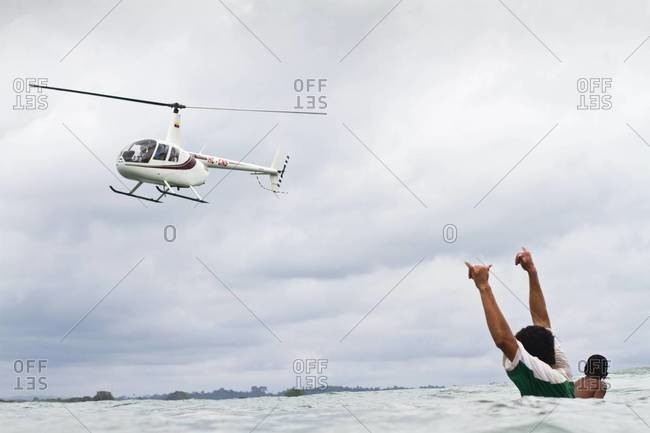 Surfer showing shaka sign to a helicopter