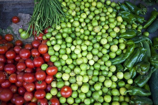 Heap of tomatoes, limes, jalapenos at farmer's market