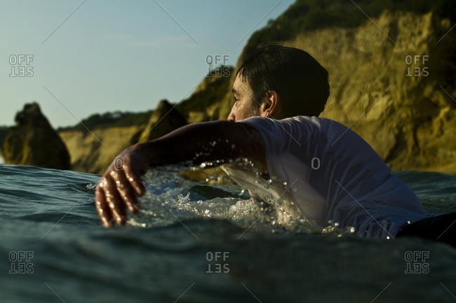 Man paddling on surfboard toward waves