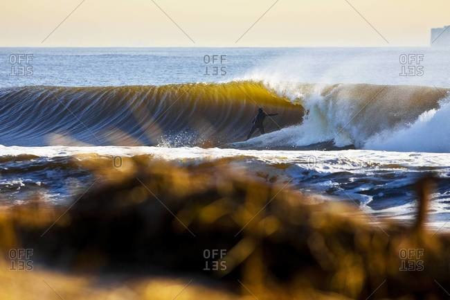 Surfer riding out of a tube