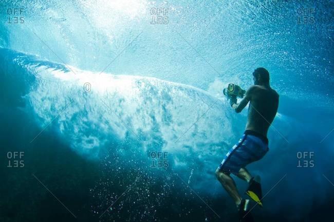 Man filming underwater at Teahupoo, Tahiti
