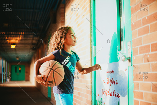 Young girl holding a basketball in a school