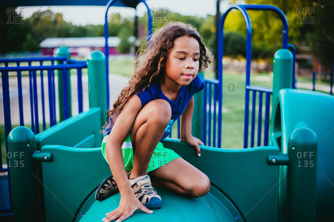Girl sitting on top of a jungle gym