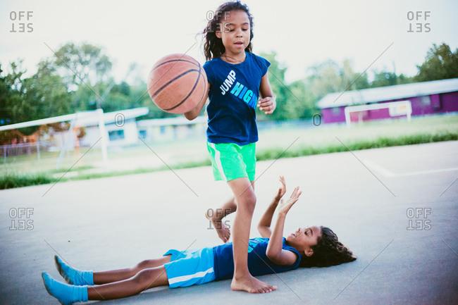 Girl dribbling over sister on  a basketball court