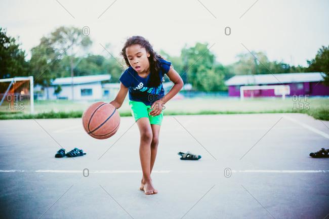 Girl dribbling basketball on a court