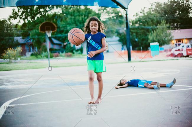 Girl dribbling while sister lies down basketball court