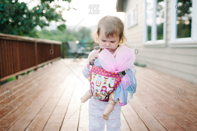 Little girl holding a doll in a baby carrier
